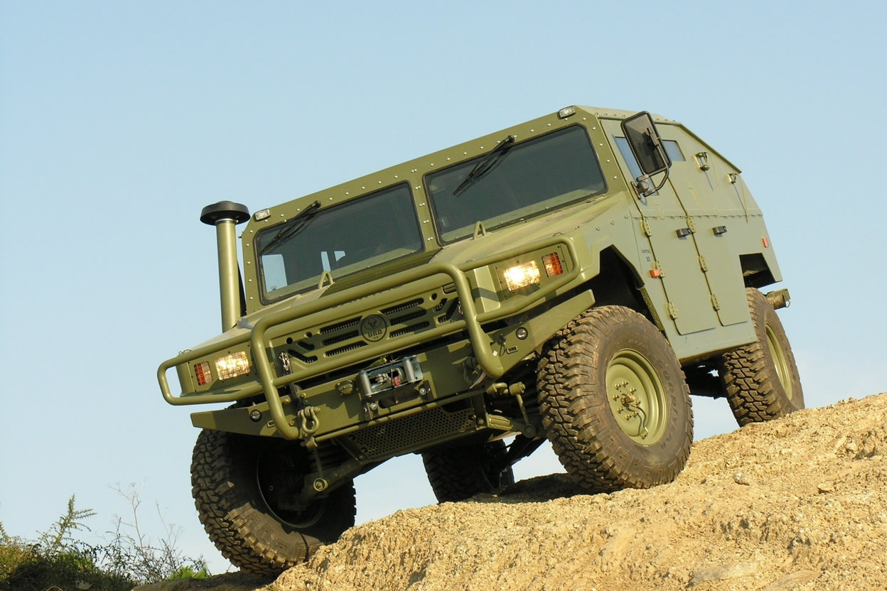 An armoured dark green coloured hummer parked on top of a hill
