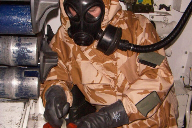 A man in a camoflauged hazmat suit wearing a gas mask and black leather gloves.